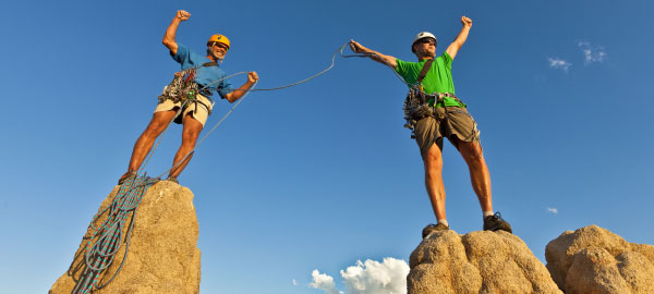 Team of 2 rock climbers with climbing ropes celebrate in victory pose after making it to the summit of rock pinnacles