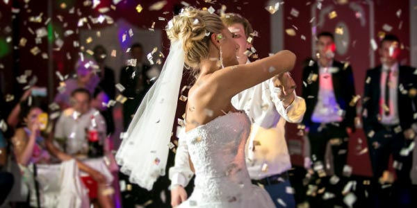 Bride and groom, showered by confetti whilst dancing at wedding reception venue whilst guests look on