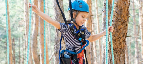 Girl navigates tree-top ropes course at school camp