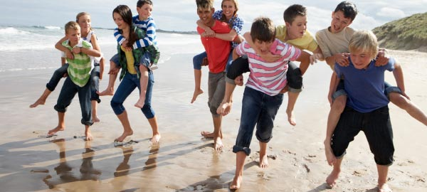 Kids piggybacking along beach on school camp