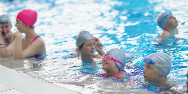 children at edge of pool, learning to swim in school swimming lesson